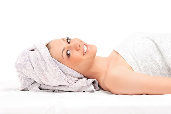 A young woman getting spa treatment isolated on white background