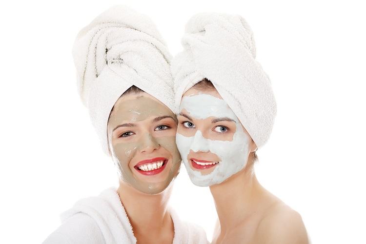 Happy two young woman with anti-aging masks . Isolated on white background.