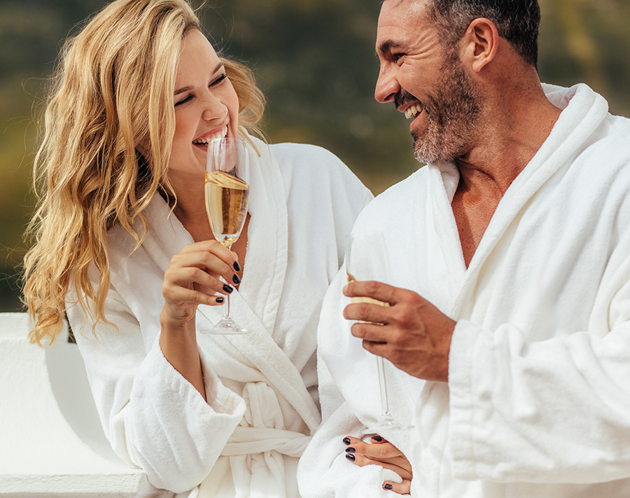 Cheerful couple in bathrobe talking and laughing in the balcony with glass of wine. Man and woman in bathrobes spending time at together.
